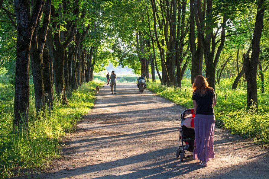 Kvinde går med barnevogn i park