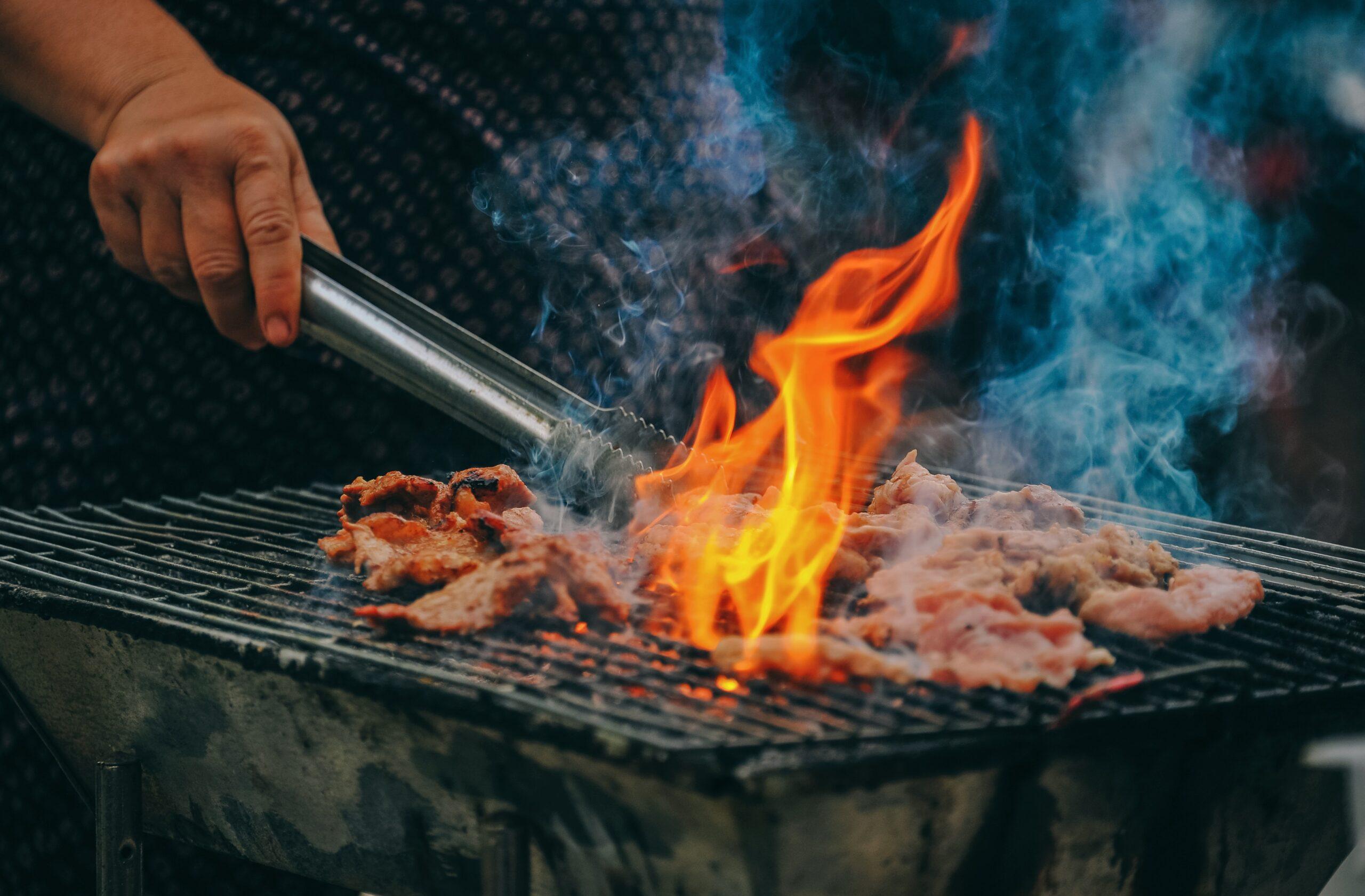 Mand griller kød på grill